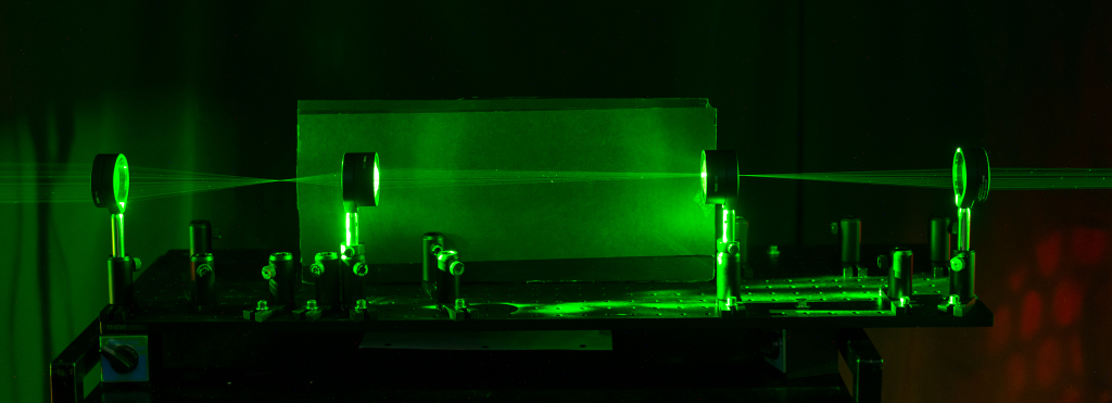 – An optical cloaking device that hides objects by taking advantage of the focal lengths of a set of lenses. The path light rays taken through the device is shown by shining a laser through the series of lenses. Picture courtesy of the University of Rochester.
