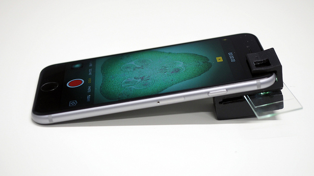A clip attached to a smartphone to facilitate microscopy, as described in the previous paragraph.