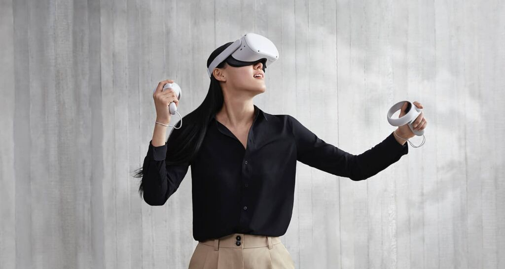 Woman plays Oculus Quest 2. She has an eyebox on and is holding hand sets in both hands. The design is sleek and white.